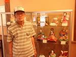 旧型雛人形の前に立つ津崎米夫さん